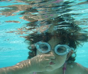 girl underwater holding her nose