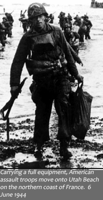 image of solider carrying gear at Utah beach