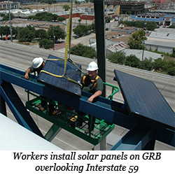 Workers install solar panels on the convention center overlooking Interstate 59