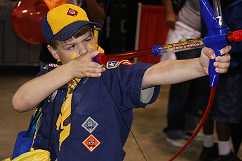 boy scout aiming an arrow