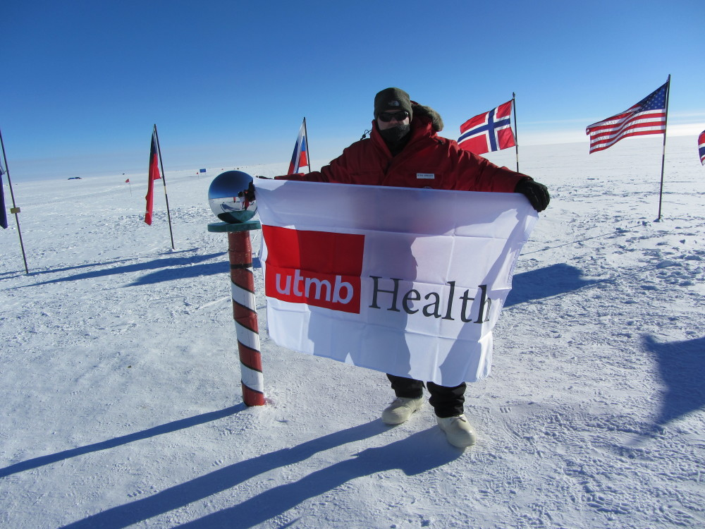 Kirk Abbott holds up a UTMB sign at the South Pole.