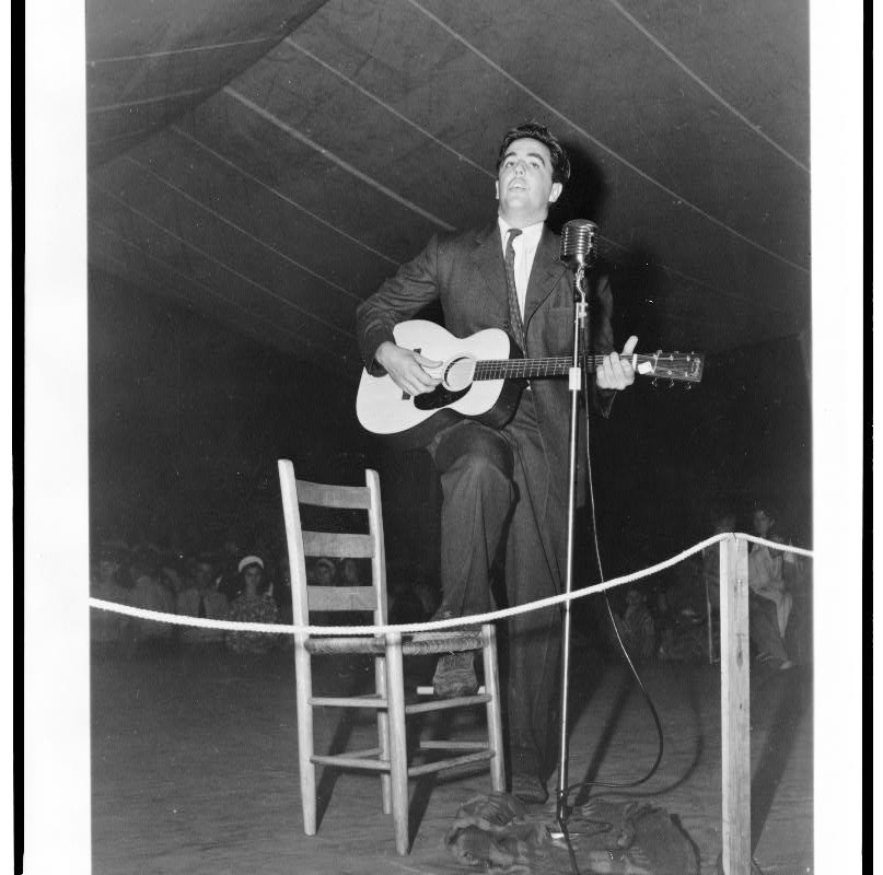 Alan Lomax playing guitar on stage