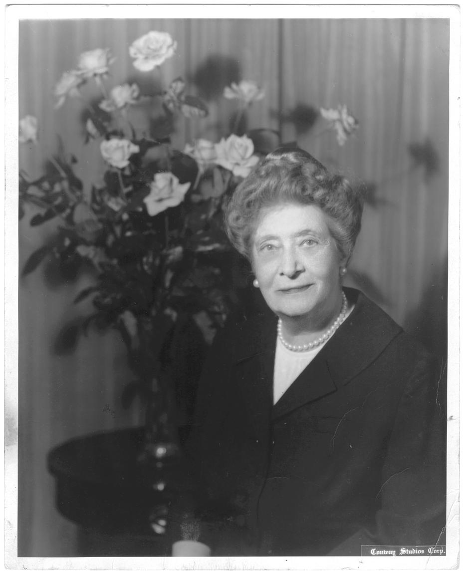 Ima Hogg seated in front of floral arrangement