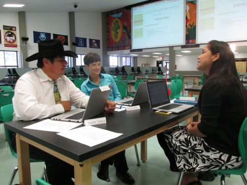 Brittany Lewis (right) coaching a couple of teachers on computer skills