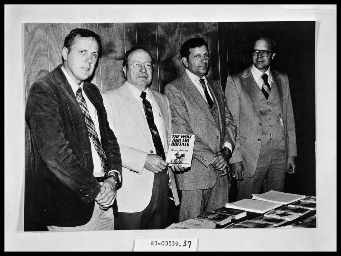 four men standing behind a book table
