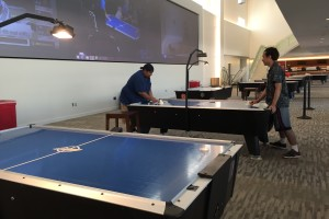 Two men stand at a table playing air hockey before the tournament begins.