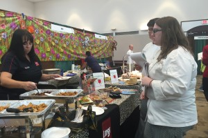Student Brooke Simmons waits in line at a booth as a vendor scoops teriyaki chicken onto a plate for her to taste.