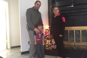 Haider Elias poses near a Christmas tree with his wife and son.