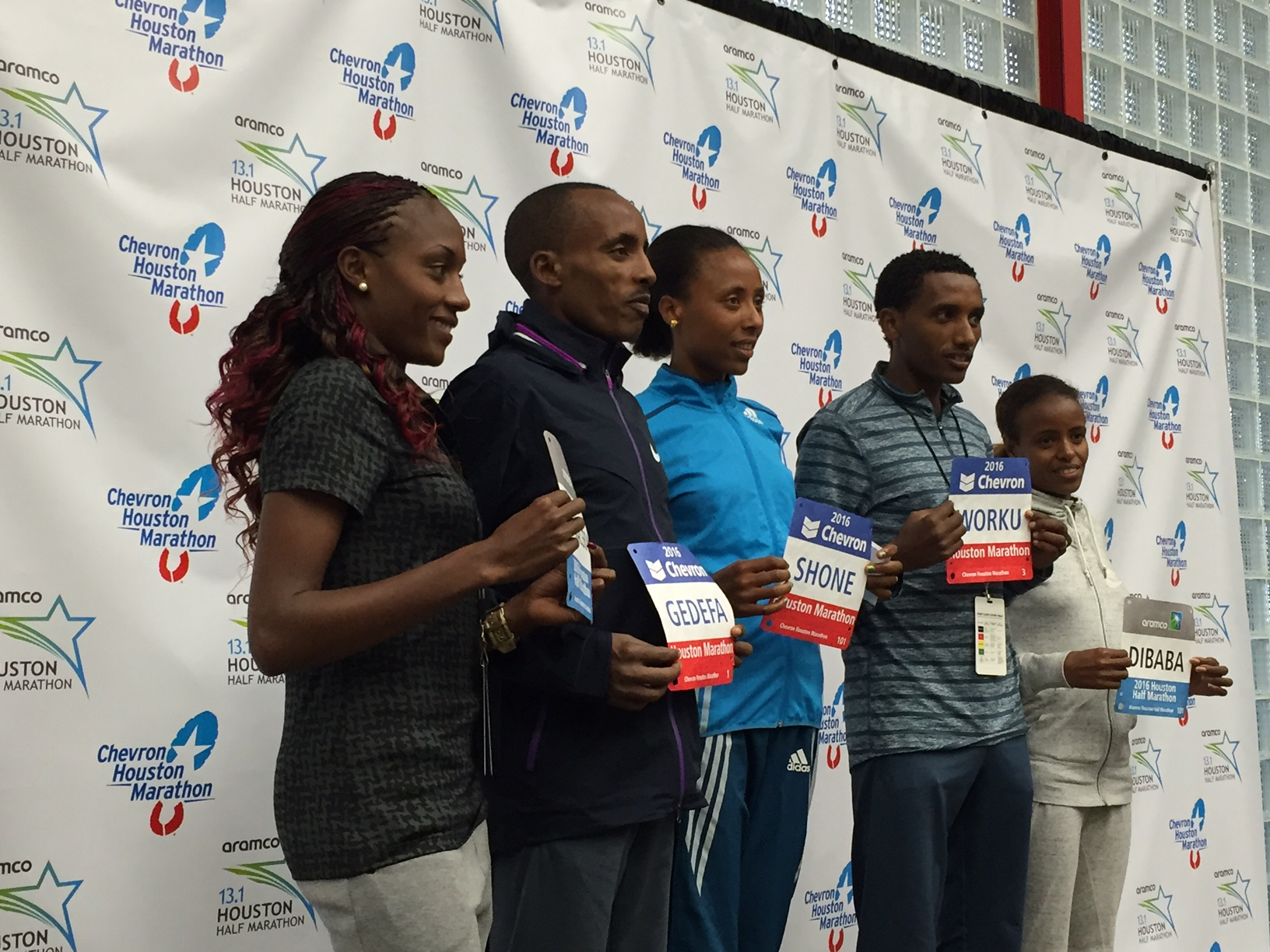 Runners pose for a picture holding their marathon bibs.