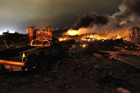 A vehicle near the remains of a fertilizer plant burning after an explosion