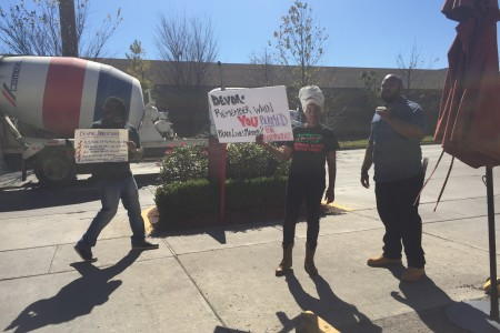 Activists hold signs in protest outside the NAACP award ceremony where Devon Anderson was honored.