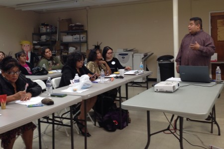 Texas Organizing Project's Alain Cisneros (right) tells workshop participants about the deferred action programs, which are commonly known by the acronyms DACA and DAPA and would temporarily stop the potential deportation of undocumented immigrants who meet certain criteria established by the federal government.