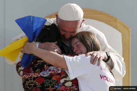 Pope Francis hugs two girls