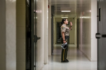A guard inside the Webb County Jail waves goodbye