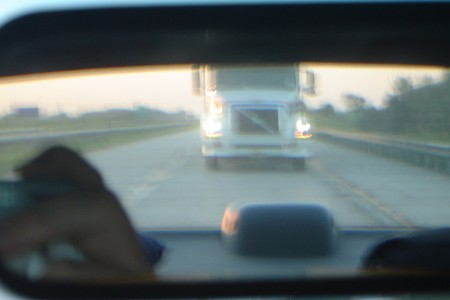 Blurred Transport Truck in Rearview Mirror as seen from Driver Perspective