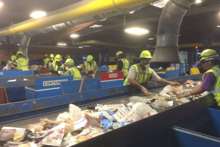 Workers separate materials for recycling.