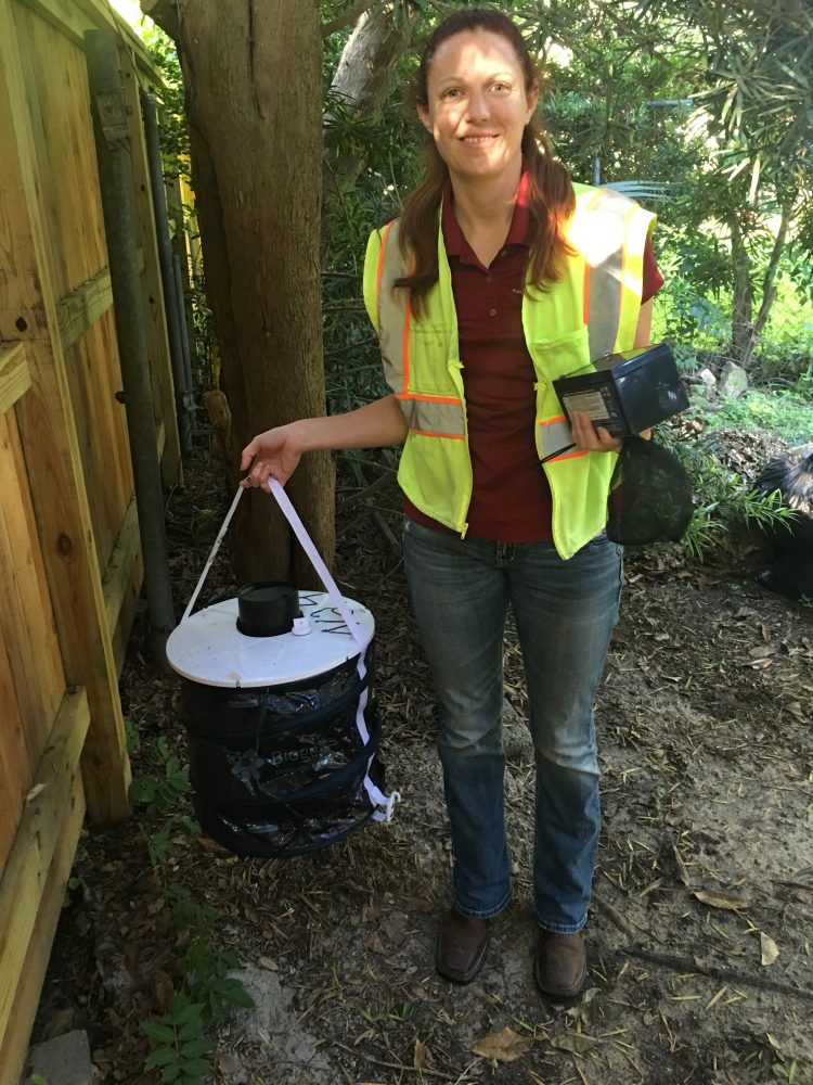 Roberts retrieves a mosquito trap from a backyard in southwest Harris County. Homeowners give permission to have traps placed on their property.