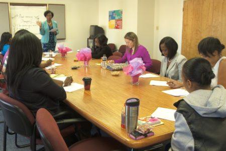 women around a table listen to speaker
